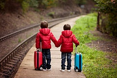 two boys railway station waiting train suitca suitcases 60385539